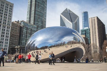 a group of people walking in front of a large city with Millennium Park in the background