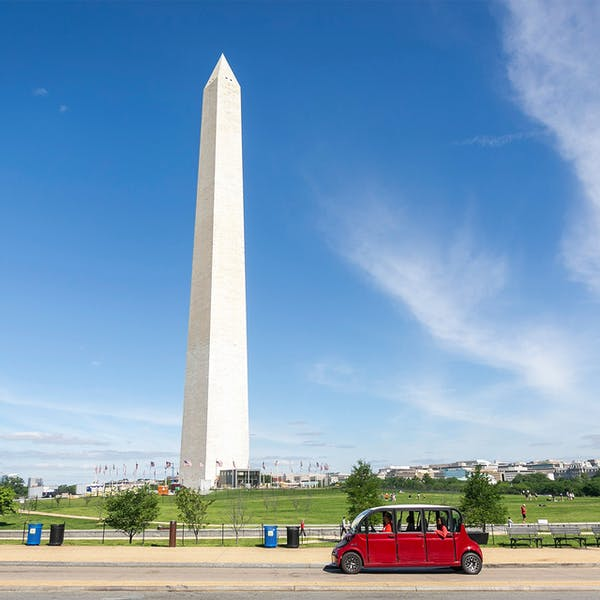 a group of people standing in a parking lot with Washington Monument in the background