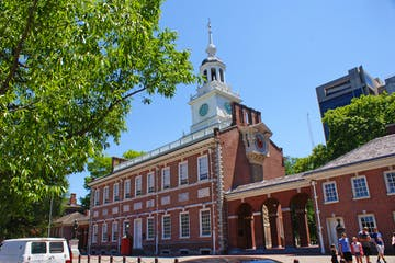 a large brick building with Independence Hall in the background