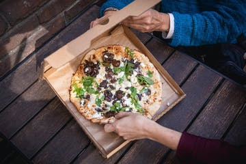 a pizza sitting on top of a wooden cutting board