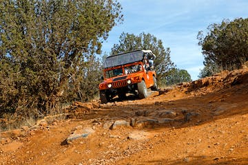 red jeep driving on rugged terrain