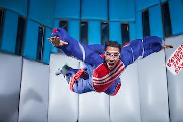 a man in a purple suit indoor skydiving