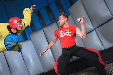 man indoor skydiving with instructor