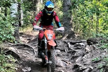 Rider in mountain area with trees around