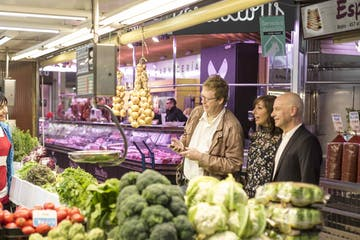 a person standing in front of a store filled with lots of fresh produce