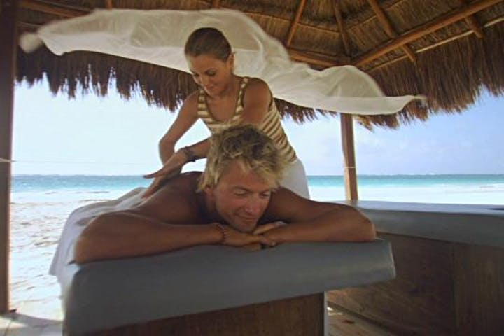 person enjoy a massage in a tropical setting