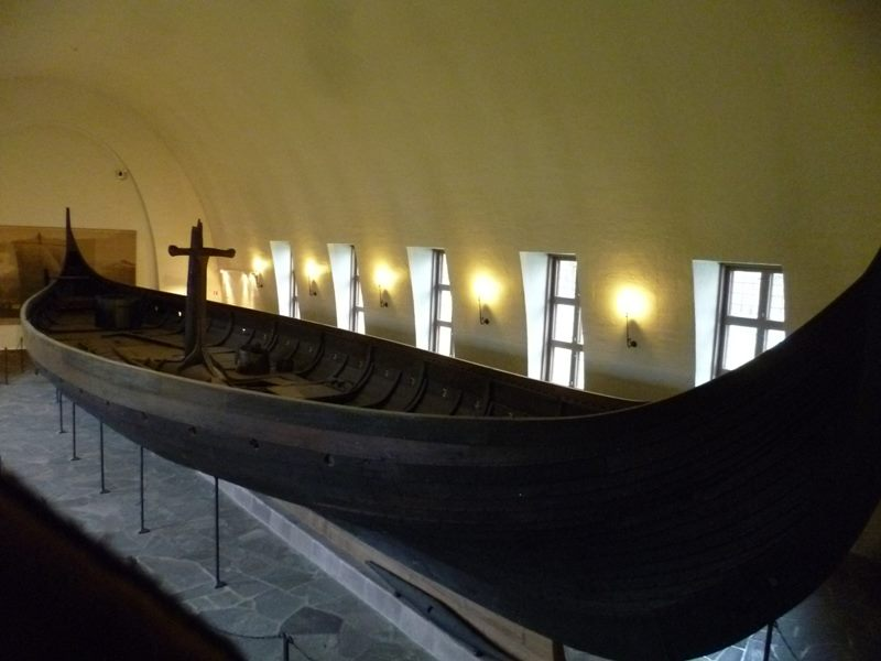 a wooden boat in a room with Viking Ship Museum in the background