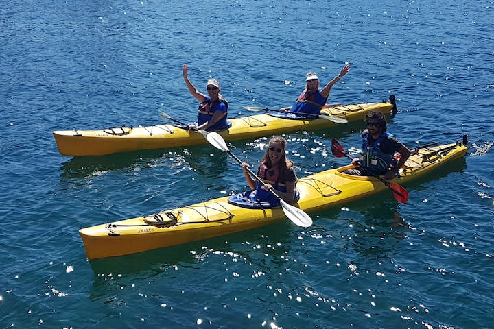 people waving from a kayak