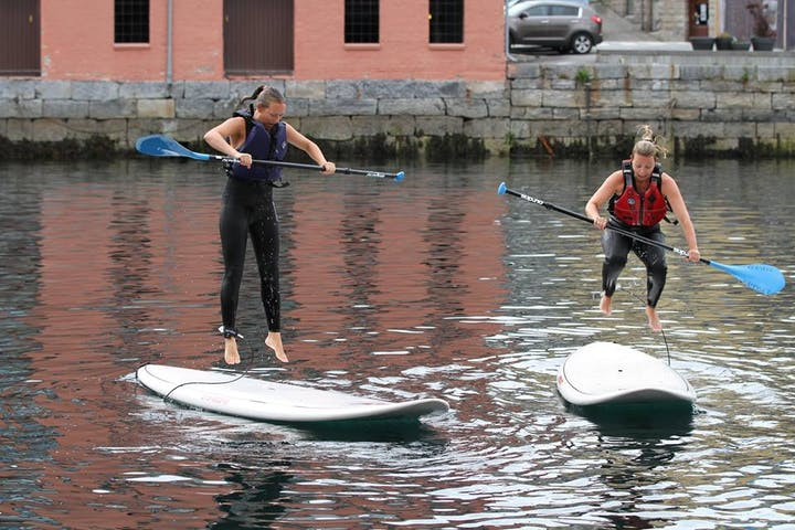 two girls jumping on a paddle board
