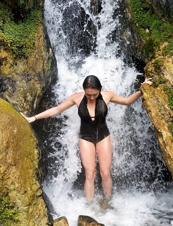 a woman standing next to a waterfall