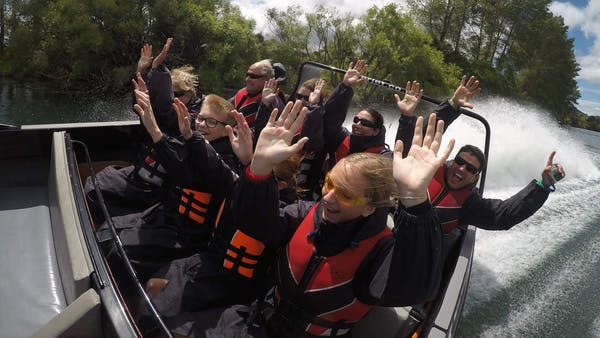 jet boat group with hands raised