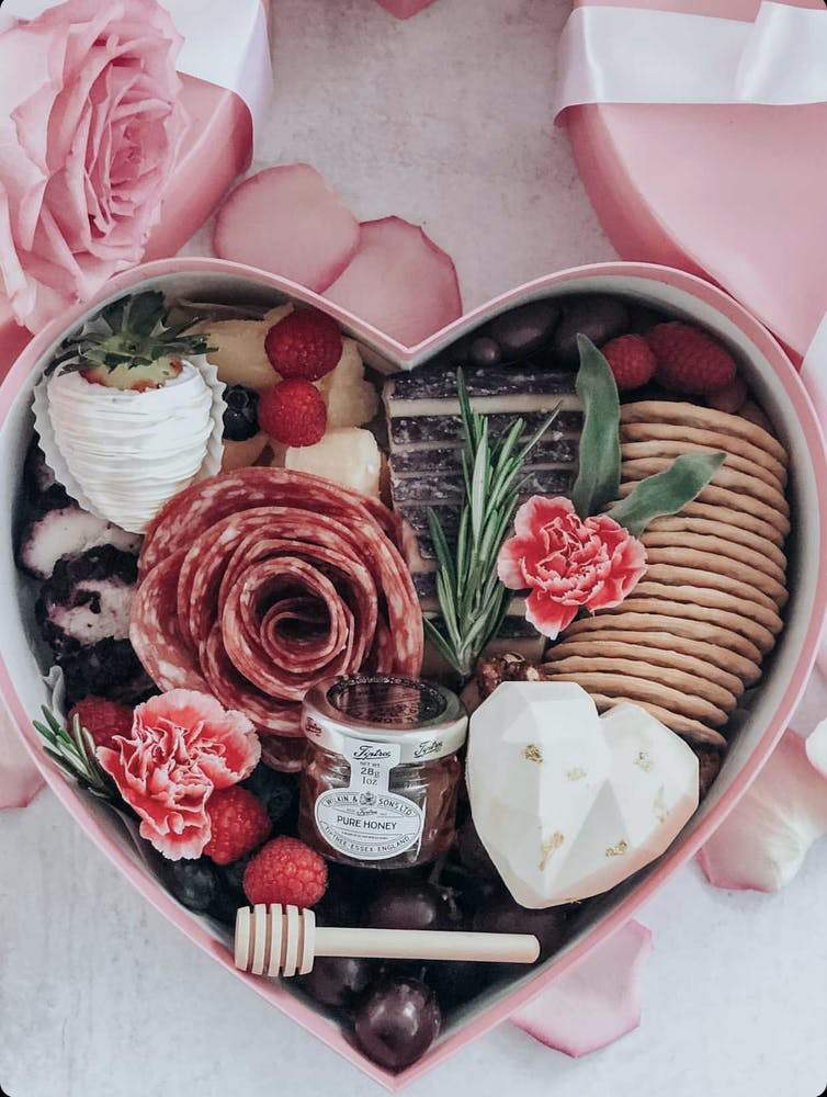 a pink box filled with different types of food on a plate
