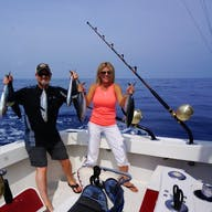A couple shows off their line of several fish from a Bite Me charter