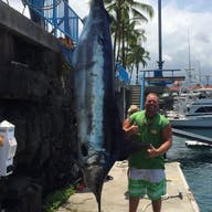 This fisher can't help but smile with this marlin over twice his height from a Bite Me 1 charter