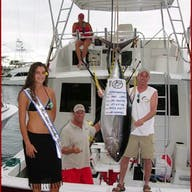 A group shows off their prize tuna catch from a Bite Me charter