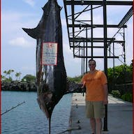 A fisher stands by his Bite Me charter marlin catch that's bigger than him