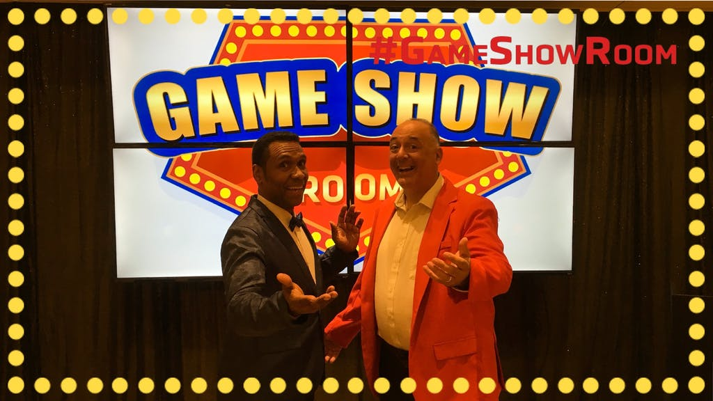 2 game show hosts posing in front of game room board