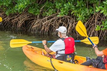 person kayaking on orange kayak
