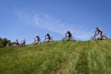 a group of people riding bikes on a grassy hill