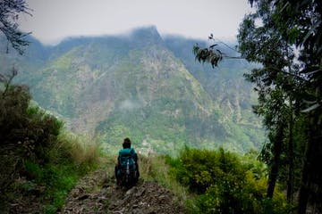a person standing in front of a mountain trail