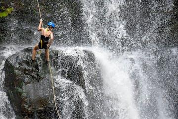 a girl rock climbing down a waterfall