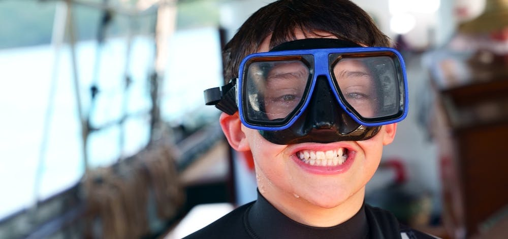 a close up of a child on a boat wearing a snorkelling mask