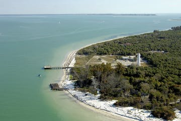 Aerial view of emerald green water and the lighthouse and beautiful beaches of Egmont Key St. Petersburg, Florida - Docks , sailboats and a pontoon boat in the waters