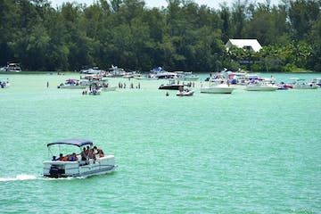Back view of boat rental with happy family visitng the crystal blue clear waters at Jewfish Key