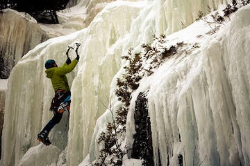 an ice climber ascending a frozen waterfall