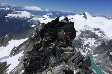 a climber on a guided trip up Forbidden Peak traverses near the summit