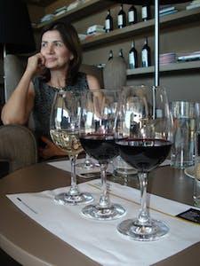persona sentada en una mesa con copas de vino