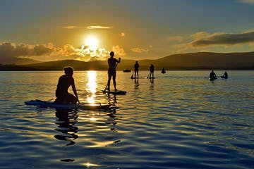 a group of people on stand up paddle boards at sunset in Dingle Harbour