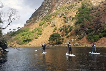 a group of people on stand up paddle boards on caragh lake
