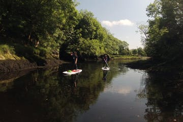 two stand up paddle boarders on a river in Kenmare