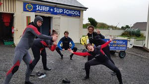 group of people in wetsuits posing in front of a surf school
