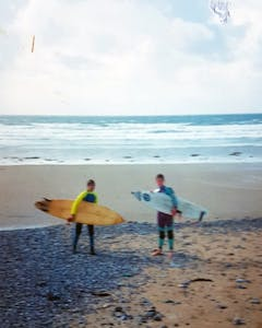two boys standing on the beach holding surfboards