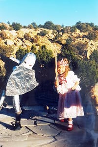 A girl in a pink dress and a boy in a knight costume playing in new mexico
