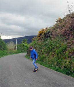 a man riding a skateboard down a country road