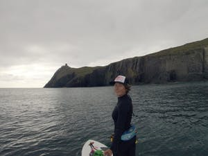 a woman stand up paddling boarding on the ocean near cliffs with a tower on top