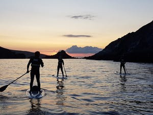 a group of stand up paddle boarders at sunset paddling at coumeenole beach ireland
