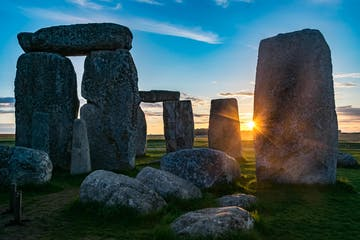 a stone building with Stonehenge in the background