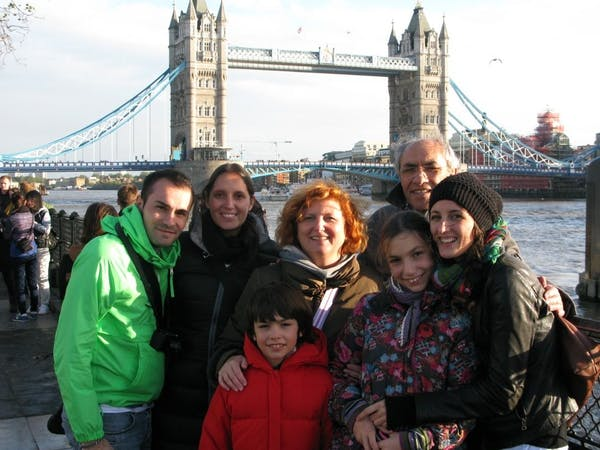 a group of people standing in front of a bridge