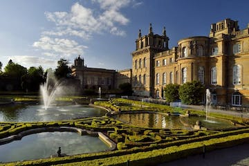 a castle with water in the background with Blenheim Palace in the background