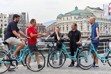 a group of people standing in front of a bicycle