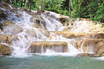 a large waterfall over some water with Dunn's River Falls in the background