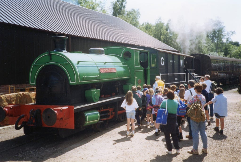 a group of people standing next to a train
