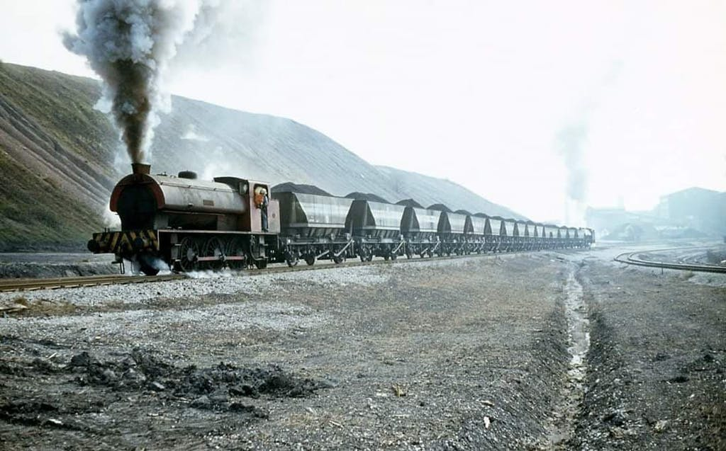 a steam train on a track with smoke coming out of it
