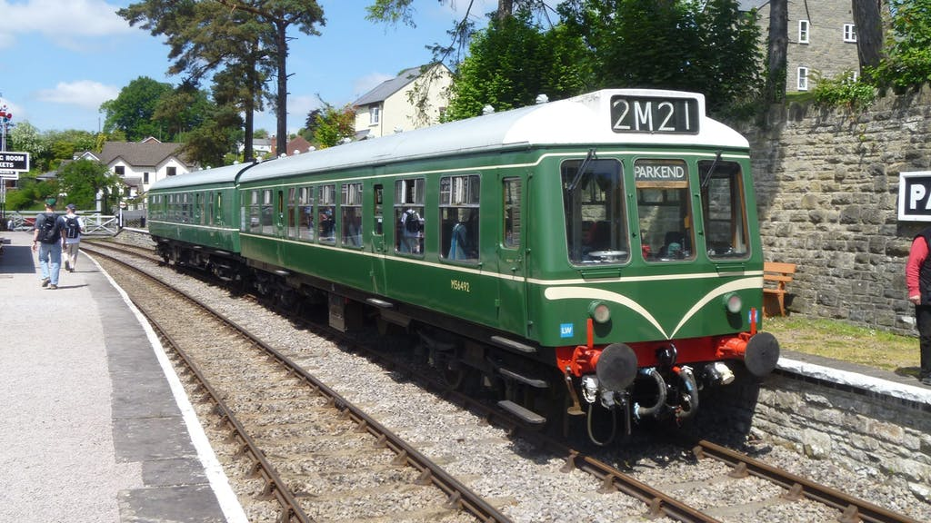 a green train that is sitting on a railroad track