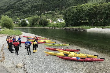 group of people standing by river going kayaking