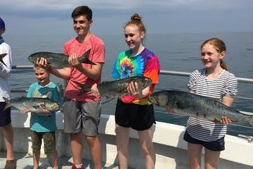 a group of people holding fish